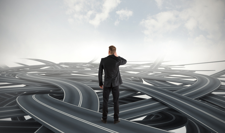 Businessman in crisis facing different roads